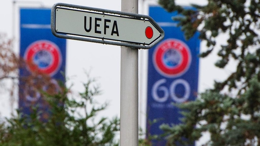 FILE - This is a Tuesday, Dec. 2, 2014 file photo of a UEFA sign pictured  at the UEFA Headquarters in Nyon, Switzerland. UEFA said Wednesday April; 6, 2016 that  it has been raided by Swiss police and has handed over evidence of a Champions League television rights contract with an offshore marketing agency implicated in the FIFA bribery scandal. (,Jean-Christophe Bott, Keystone File, via AP)