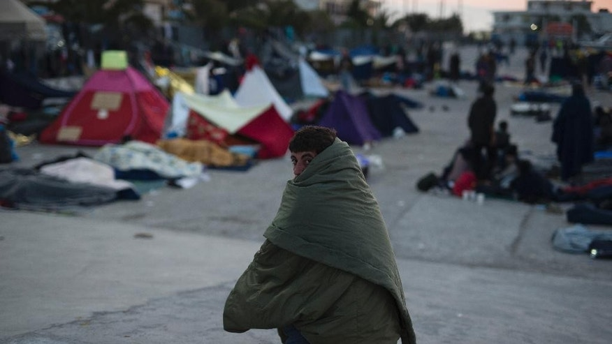A Migrant covered with a sleeping bag looks on at the port of the Greek island of Chios, Wednesday, April 6, 2016. Authorities said that more than 1700 migrants and refugees are in the island. (AP Photo/Petros Giannakouris)