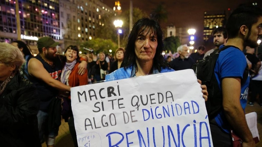 "A woman holds a sign that reads in Spanish ""Macri if you have any dignity, resign,"" during a protest against President Mauricio Macri outside the government in Buenos Aires, Argentina, Thursday, April 7, 2016. An Argentine prosecutor on Thursday asked for an investigation into President Macri's role in offshore companies, adding to the global fallout from a massive leak of documents from a Panama law firm. (AP Photo/Natacha Pisarenko)"