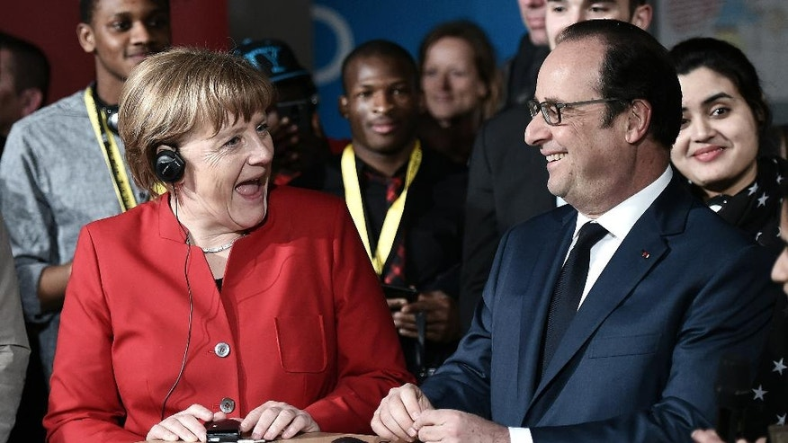 "French President Francois Hollande, right, and German Chancellor Angela Merkel smile as they end their discussions  referred to as the ""Cafe du Monde"" talks  organized by the Franco-German Youth Office (OFAJ) Thursday, April 7, 2016 in Metz, eastern France, during a Franco-German cabinet meeting. (Frederick Florin, Pool via AP)"