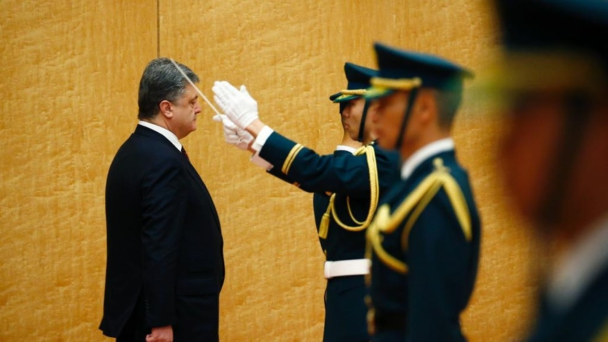 Ukrainian President Petro Poroshenko, left, inspects an honor guard before talks with Japan's Prime Minister Shinzo Abe at Abe's official residence in Tokyo, Wednesday, April 6, 2016. Poroshenko, who was in Japan to meet Abe and business leaders, defended himself earlier in the day in the massive leak of records on offshore accounts that has named political officials, business and celebrities from around the world. (Thomas Peter/Pool Photo via AP)