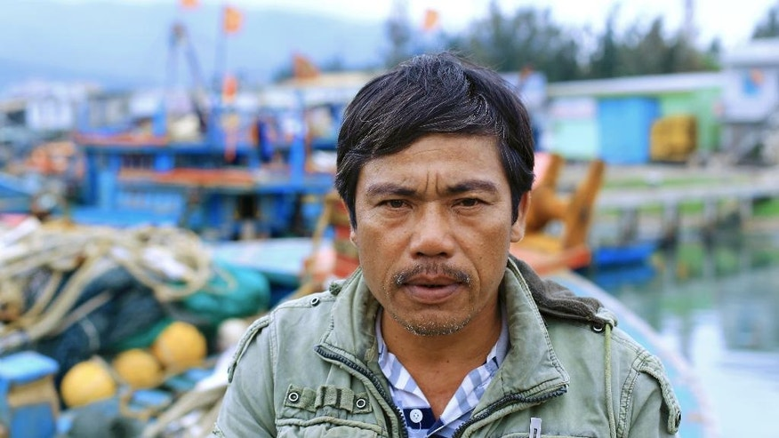 In this March 26, 2016, photo, Vietnamese fisherman Tran Lan poses for a photo in front of his boat in Tho Quang port, Danang, Vietnam. For five generations, Tran Lan's family has been fishing in the South China Sea. (AP Photo/Hau Dinh)