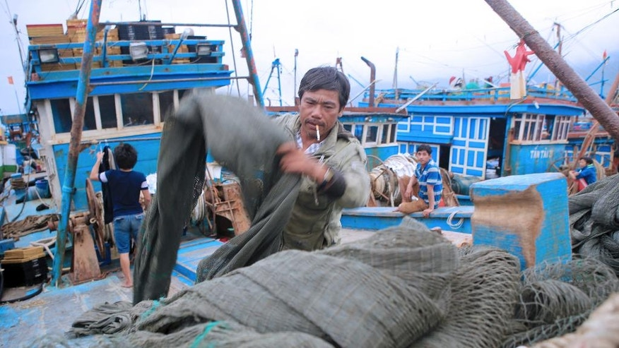 In this March 26, 2016, photo, Vietnamese fisherman Tran Lan piles fishing nets on his boat in Tho Quang port, Danang, Vietnam. For five generations, Tran Lan's family has been fishing in the South China Sea.(AP Photo/Hau Dinh)