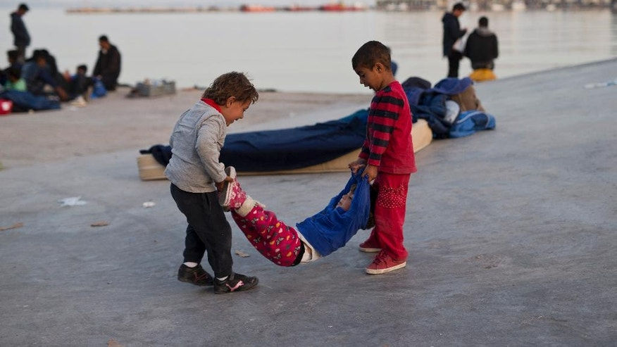 Children play at the port of the Greek island Chios, Wednesday, April 6, 2016. Volunteers are concerned about children's health of some 300 migrants and refugees who managed to leave the VIAL detention center on the island a few days ago. Authorities said that more than 1,700 migrants and refugees are on the island. (AP Photo/Petros Giannakouris)