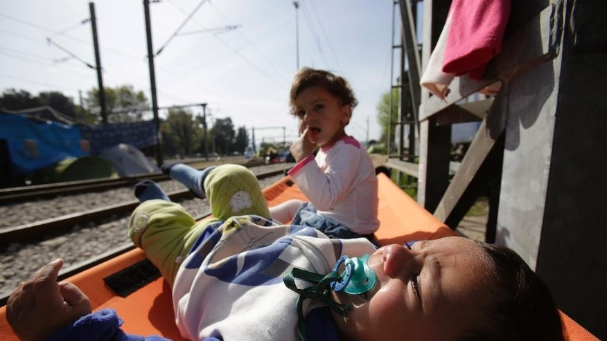 Migrant baby sleeping near train wagon at the border crossing at the northern Greek border point of Idomeni, Greece, Thursday, April 7, 2016. Migrants and refugees stranded in Idomeni, find shelter in train 'sleeping cars'. About 11,000 migrants remain stuck in Idomeni, most of them for over a month, not knowing how to deal with the shut European borders. (AP Photo/Amel Emric)