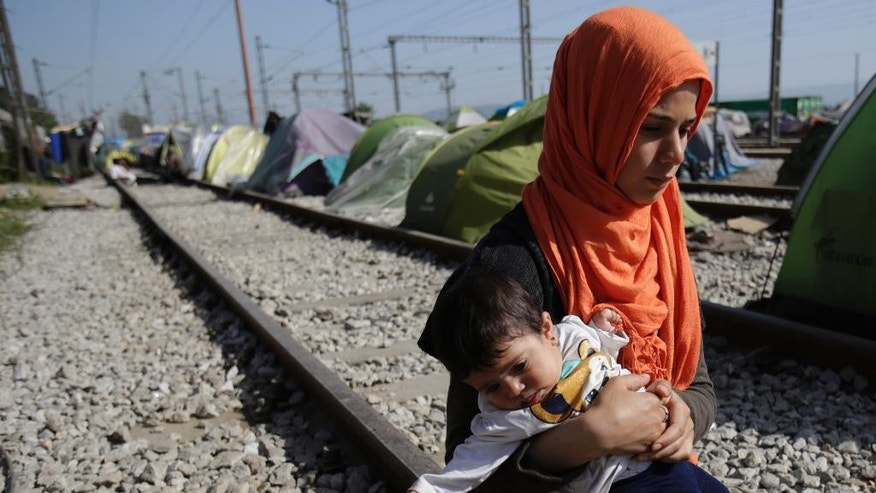 Migrant woman Kais Khalaf, 25, from Syria, holds her 7-month old daughter at the border crossing at the northern Greek border point of Idomeni, Greece, Thursday, April 7, 2016.  Migrants and refugees stranded in Idomeni, find shelter in train 'sleeping cars'. About 11,000 migrants remain stuck in Idomeni, most of them for over a month, not knowing how to deal with the shut European borders. (AP Photo/Amel Emric)