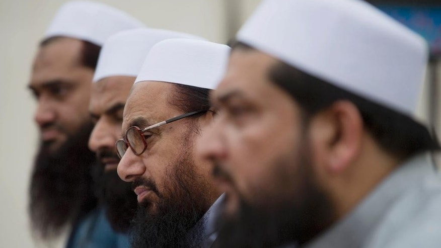 FILE- In this Monday, Nov. 2, 2015 file photo, Hafiz Saeed, second from right, chief of Pakistani religious group Jamaat-ut-Dawa listens to reporters at a news conference in Islamabad, Pakistan. Reports have surfaced in the Pakistani city of Lahore that a charity run by the militant group Lashkar-e-Taiba has established an Islamic court separate from the regular judiciary. The spokesman of the Jamaat-ud-Dawa charity claims it's not a parallel judicial system but that the court works with the consent of two rival parties to decide disputes. (AP Photo/B.K. Bangash, File)