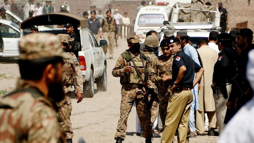 Pakistani police officers and soldiers cordon off the area following a bomb blast in Peshawar, Pakistan, Thursday, April 7, 2016. Police officer Jamshed Khan said a bomb targeting police at a checkpoint near the northwestern city of Peshawar killed a police officer and injured other. (AP Photo/Mohammad Sajjad)