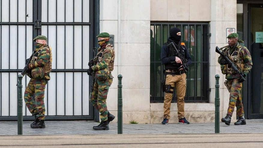 "A police man and soldiers stand guard as terror suspect Salah Abdeslam's case appears in court at a justice building in Brussels on Thursday, April 7, 2016.  The lawyer for Paris attacks suspect Salah Abdeslam said Thursday from Brussels that it would take ""some weeks"" before his client would be extradited to France.  (AP Photo/Geert Vanden Wijngaert)"