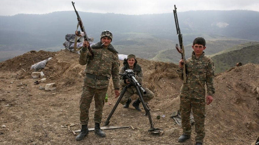 Armenian soldiers pose near a frontline in Nagorno-Karabakh, Azerbaijan, Wednesday, April 6, 2016. A cease-fire largely held Wednesday around Nagorno-Karabakh after an outburst of fighting that raised fears of a new all-out war between Azerbaijani and Armenian forces. (Karo Sahakyan/PAN Photo via AP)