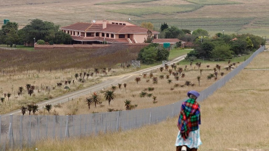 FILE - In this Tuesday, May 24, 2011 file photo, a woman passes the rural home of the late former president Nelson Mandela in Qunu, South Africa. A South African court ruled Thursday, April 7, 2016 that Mandela's ex-wife Winnie Madikizela-Mandela has no rights to his rural home. Mandela's third wife Graca Machel was the main beneficiary. (AP Photo/Schalk van Zuydam, File)