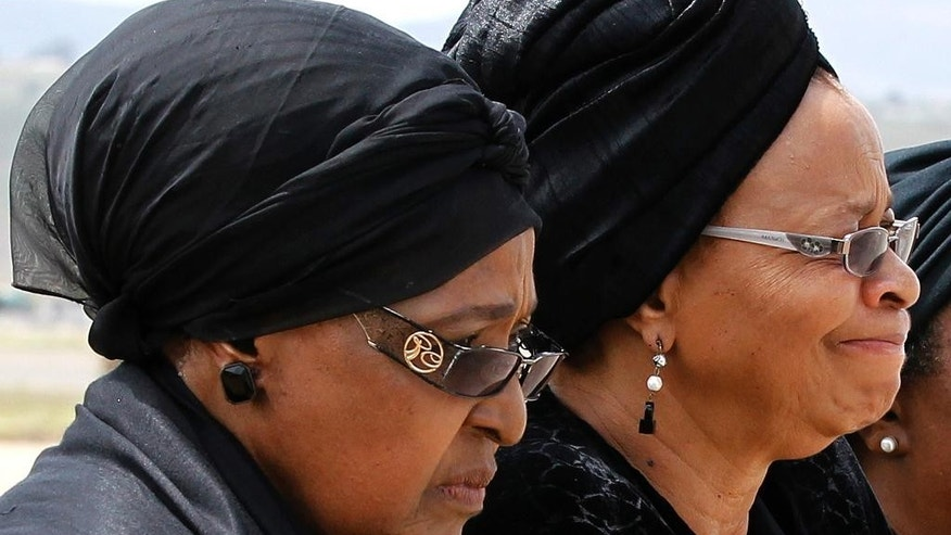 FILE - In this Dec. 14, 2013 file photo, Winnie Madikizela-Mandela, left, Nelson Mandela's former wife, and Nelson Mandela's widow Graca Machel watch as the former South African president's casket arrives at the Mthatha airport, South Africa near Mandela's hometown of Qunu. A South African court ruled Thursday, April 7, 2016 that Mandela's ex-wife Winnie Madikizela-Mandela has no rights to his rural home. Mandela's third wife Graca Machel was the main beneficiary. (Siphiwe Sibeko/Pool Photo via AP, file)