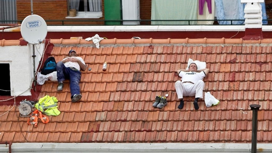 "FILE - In this Oct. 10, 2012 file photo, two workers take a nap on a roof in Madrid, Spain. Political parties are promising to turn the clock back in Spain and eliminate a time quirk dating from World War II, a move that could radically change Spaniards' eating and sleeping habits, including the celebrated siesta. Until the 1940s, Spain was on the same Greenwich Mean Time as Britain and Portugal, being in roughly the same latitude. ""We cannot lose contact with Europe. The rationalization of the timetables of work shifts and government institutions is of capital importance,"" Spain's acting Prime Minister Mariano Rajoy said last April 2, 2016. (AP Photo/Alberto Di Lolli, File)"