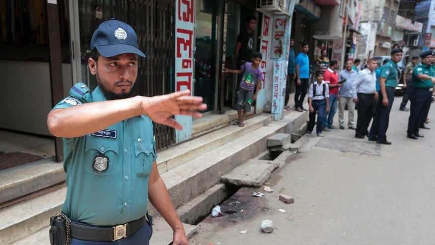 A Bangladeshi policeman stands guard at the spot where three motorcycle-riding assailants hacked student activist Nazimuddin Samad to death as he walked with a friend, in Dhaka, Bangladesh, Thursday, April 7, 2016. Police suspect 28-year-old Samad was targeted for his outspoken atheism in the Muslim majority country and for supporting a 2013 movement demanding capital punishment for war crimes involving the country's independence war against Pakistan in 1971, according to Dhaka Metropolitan Police Assistant Commissioner Nurul Amin. ( AP Photo)