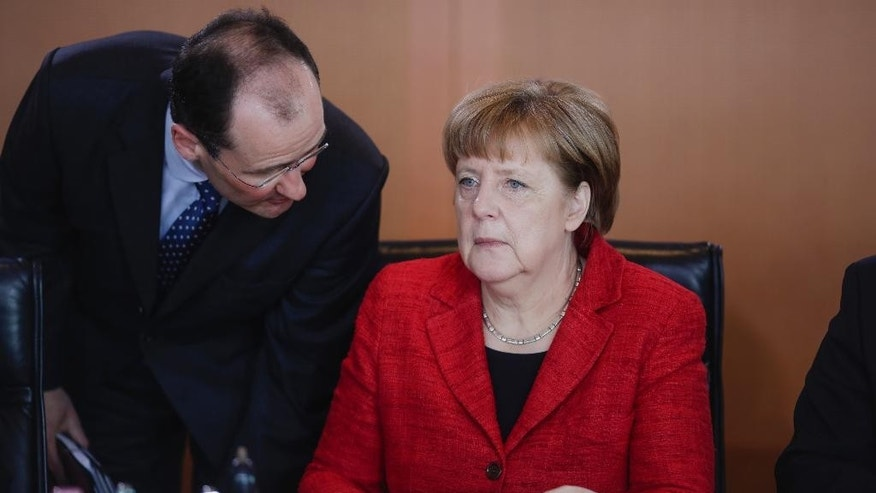 German Chancellor Angela Merkel, right, listens to her deputy office leader Bernhard Kotsch after she arrived for the German government's weekly cabinet meeting at the chancellery in Berlin, Germany, Wednesday, April 6, 2016. (AP Photo/Markus Schreiber)