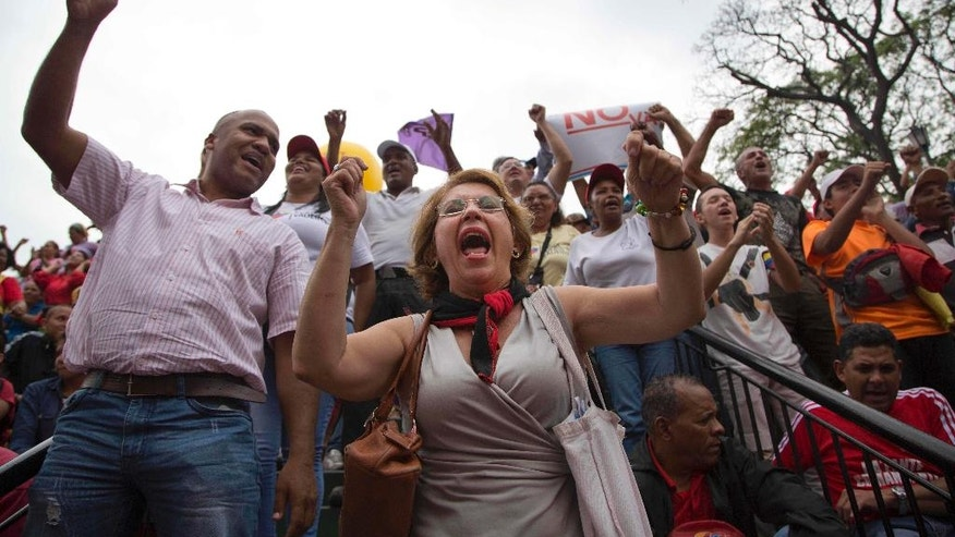 Supporters of President Nicolas Maduro yell out slogans during a demosntration, at Miraflores Presidential Palace in Caracas, Venezuela, Thursday, April 7, 2016. Groups allied to Venezuela's socialist administration marched to protest an amnesty law passed by the opposition controlled congress calling for release of those it deems to be political detainees. (AP Photo/Ariana Cubillos)