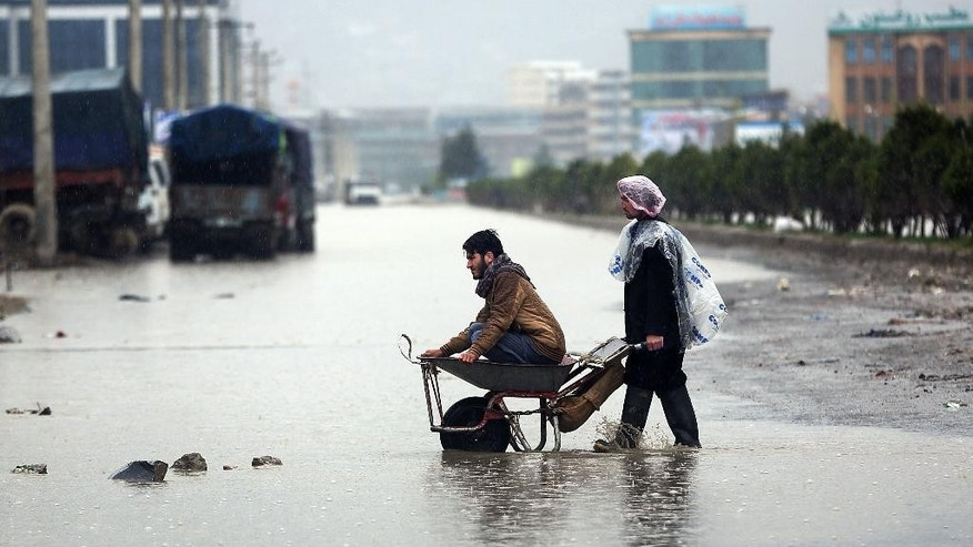 "FILE - In this Saturday, April 2, 2016 file photo, Afghans make their way in flooded water from heavy rain  in Kabul, Afghanistan. ""People are not satisfied with the current government and its leaders, some even hate this government because neither of the leaders have fulfilled the promises they made,"" says Ishaq Gailani, leader of the National Solidarity Movement of Afghanistan and a former lawmaker. But, he added, ""you can't implement democracy in Afghanistan overnight, you need more time."" (AP Photo/Massoud Hossaini, File)"