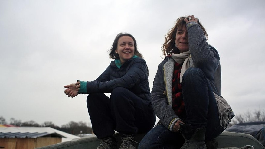 In this Feb. 4, 2016 photo, volunteer Liz Clegg, right, poses with her daughter Inca Sorrell, in the migrant camp of Calais, north of France. The text message from a young boy, writing in broken English on a no-frills cellphone, was frightening enough to set off a frantic, trans-Atlantic search that saved the lives of 15 migrants trapped in a locked truck in England. The message flashed on the cellphone of volunteer Liz Clegg, who in March had handed out hundreds of basic cellphones to children living in the squalid migrant camp in Calais, France, and told them to text in any crisis. (AP Photo/Thibault Camus)