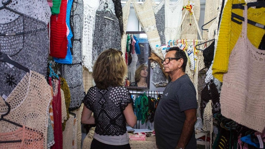 In this April 4, 2016 photo, salesman Victor Rodriguez helps a customer at his stall in the Almacenes San Jose in Havana, Cuba. Rodriguez imagines a future Cuban economy where he can import large quantities of thread, export his women's clothing to other countries and not have to worry about obtuse state regulations governing everything down to where exactly he can place items at his small retail stand. (AP Photo/Desmond Boylan)