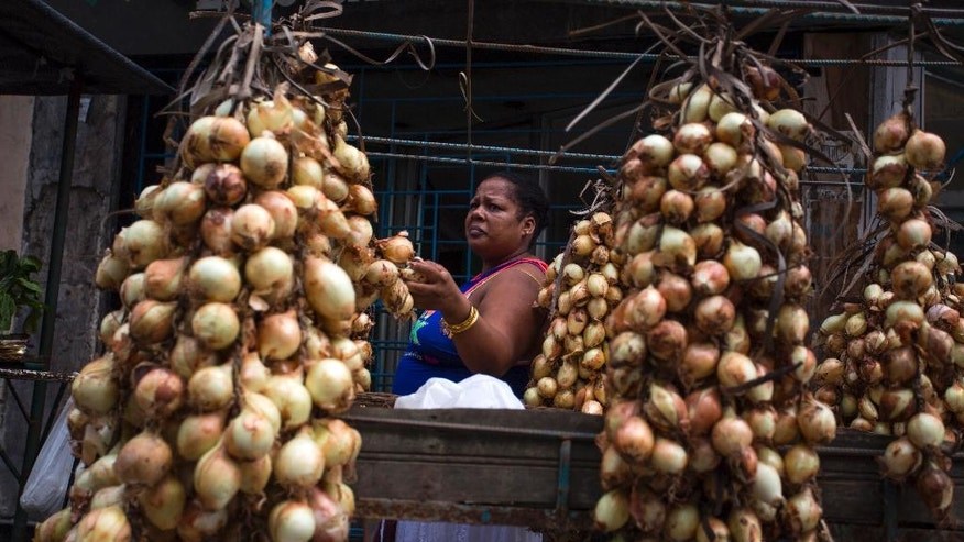 In this April 4, 2016 photo, a woman shops for onions from a private stall on a street in Havana, Cuba. Many Cubans are anxious to see their economy grow; the vast majority struggle to meet daily needs, with state workers earning an average of $20 per month. (AP Photo/Desmond Boylan)