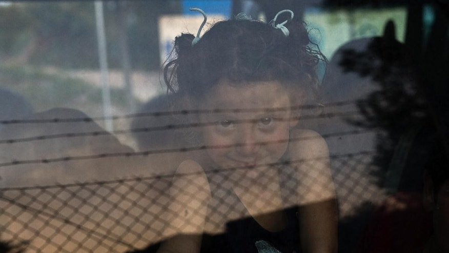 A girl looks out from a window in a mini bus as she arrives with her family to Karatepe municipality camp for refugees, on the Greek island of Lesbos, Thursday April 7, 2016. 135 refugees and migrants have been transferred Thursday to the camp from Moria detention center which hosts families and vulnerable people. (AP Photo/Petros Giannakouris)