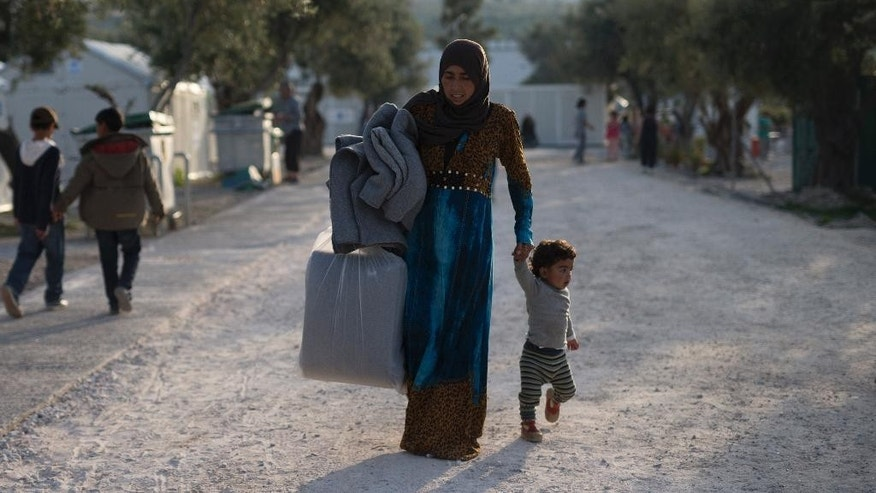 A woman and her child arrive in the Kara Tepe municipality camp for refugees in the Greek island of Lesbos, Thursday April 7, 2016. 135 refugees and migrants have been transferred Thursday from Moria detention to Kara Tepe camp center which hosts families and vulnerable  people. (AP Photo/Petros Giannakouris)