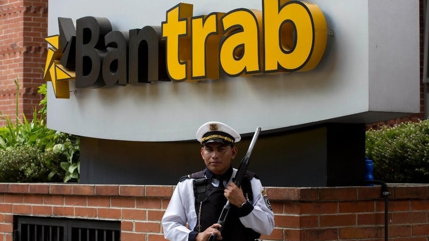 "A private security guard stands in front of a Banco de los Trabajadores building in Guatemala City, Friday, April 8, 2016. Guatemalan prosecutors have raided the offices of the mixed-capital bank as part of a money-laundering probe involving an account in the name of a Venezuelan national. The case is not related to this week's ""Panama Papers"" leak of documents related to offshore accounts. (AP Photo/Moises Castillo)"