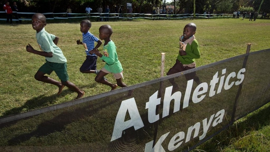 FILE - In this Sunday, Jan. 31, 2016 file photo, junior athletes run past a sign for Athletics Kenya at the Discovery cross country races in Eldoret, western Kenya. The IAAF's ethics board, in a statement issued Friday, April 8, 2016, rejected a challenge from Athletics Kenya CEO Isaac Mwangi against his provisional suspension for allegedly soliciting bribes from two athletes. (AP Photo/Ben Curtis, FILE)