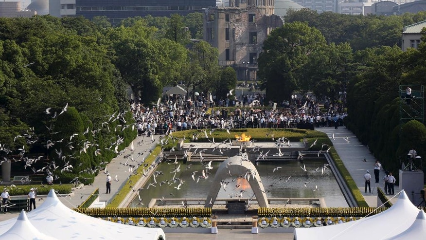 FILE - In this Aug. 6, 2015, file photo, doves fly over the cenotaph dedicated to the victims of the atomic bombing at the Hiroshima Peace Memorial Park during the ceremony to mark the 70th anniversary of the bombing in Hiroshima, western Japan. U.S. Secretary of State John Kerry will become the highest-ranking American government official to visit Hiroshima, where 140,000 Japanese died from the first of two atomic bombs dropped by his country in the closing days of World War II more than 70 years ago. Kerry and the other Group of Seven foreign ministers are scheduled to visit the Hiroshima Peace Park on Monday, April 11, 2016 and lay flowers to honor the dead. At least in Japan, the event will likely overshadow the rest of the foreign ministers' annual two-day meeting, where terrorism, maritime security and nuclear non-proliferation will be discussed. (AP Photo/Eugene Hoshiko, File)