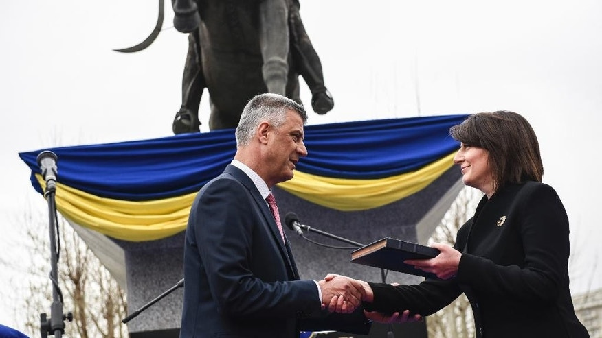 Kosovo's newly elected President Hashim Thaci, left, receives the Kosovo constitution from outgoing President Atifete Jahjaga,during the Presidential inauguration ceremony in Pristina on Friday April 8, 2016. Opposition supporters in Kosovo launched tear gas Friday to try to disrupt the inauguration ceremony for the country's new president, Hashim Thaci. (Armend Nimani, Pool via AP)