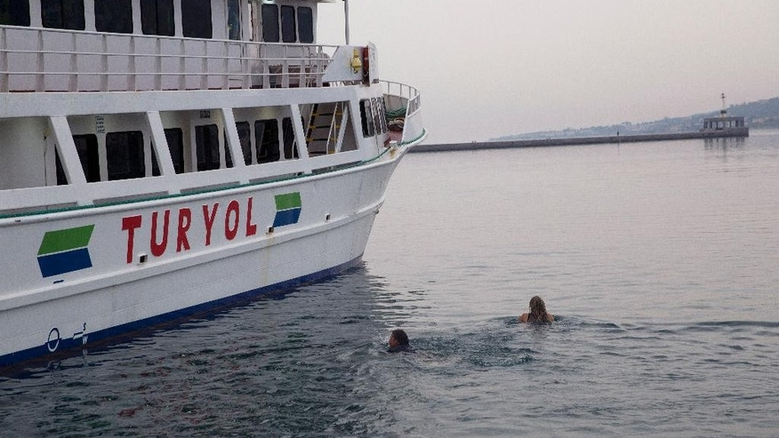 Activists swim as they try to interfere the deportation of Pakistani migrants on board a ferry set to sail for Turkey in the port of Mytilini of the Greek island of Lesbos, Friday, April 8, 2016. Forty-five migrants from Pakistan were deported to Turkey on Friday under the EU agreement with Turkey. (AP Photo/Petros Giannakouris)