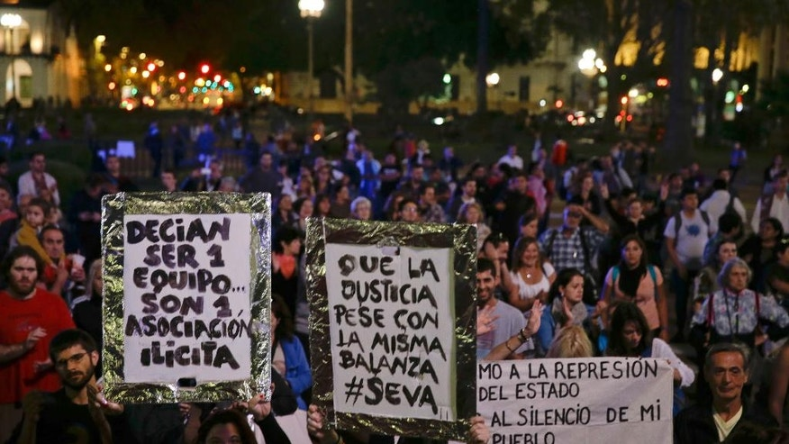 "Demonstrators protest against President Mauricio Macri outside the government  in Buenos Aires, Argentina, Thursday, April 7, 2016. An Argentine prosecutor on Thursday asked for an investigation into President Macri's role in offshore companies, adding to the global fallout from a massive leak of documents from a Panama law firm. The signs held by the protesters read in Spanish from left, ""They said they were a team... It turned out they were an illicit association."" ""Let justice weigh them with the same scales."" (AP Photo/Natacha Pisarenko)"