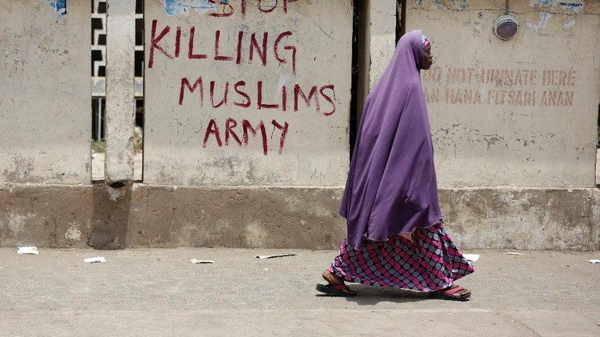 "A Muslim woman walks past a sign reading ""Stop killing Muslims Army"" on the walls in Kano, Nigeria, Friday, April. 8, 2016. A human rights lawyer says the detained leader of Nigeria's Shiite Muslims has been left near-blind and suffered several operations to remove bullets from gunshots in an army raid on his home. (AP Photo/Sunday Alamba)"