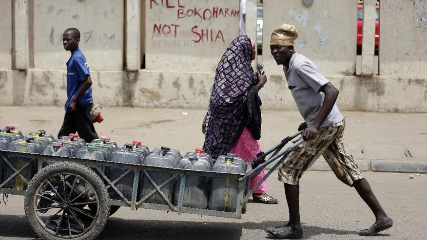 "A man pushes a cart filled with water bottles past a sign reading ""Kill Boko Haram not shia"" in Kano, Nigeria, Friday, April 8, 2016. A human rights lawyer says the detained leader of Nigeria's Shiite Muslims has been left near-blind and suffered several operations to remove bullets from gunshots in an army raid on his home. (AP Photo/Sunday Alamba)"