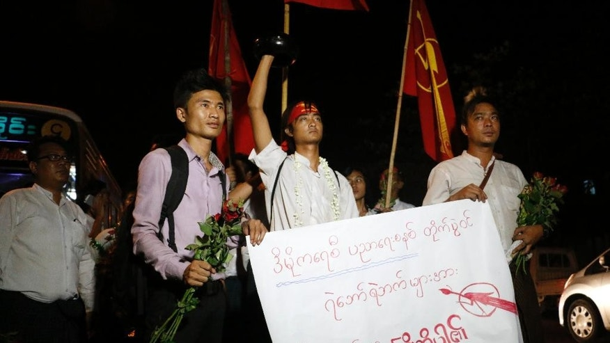 Phyo Dana, center, a student protester who recently released from Thayarwaddy Prison with President's pardon, holds an alms bowl upside-down, symbol of protest, during a gathering near Shwedagon pagoda Friday, April 8, 2016, in Yangon, Myanmar. (AP Photo/Thein Zaw)