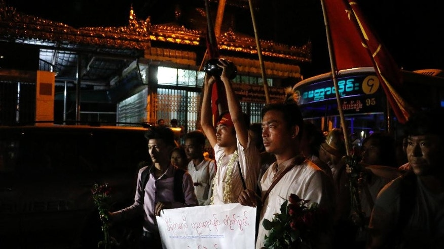 Phyo Dana, center, a student protester who was recently released from Thayarwaddy Prison with President's pardon, holds an alms bowl upside-down, symbol of protest, during a gathering near Shwedagon pagoda Friday, April 8, 2016, in Yangon, Myanmar. (AP Photo/Thein Zaw)