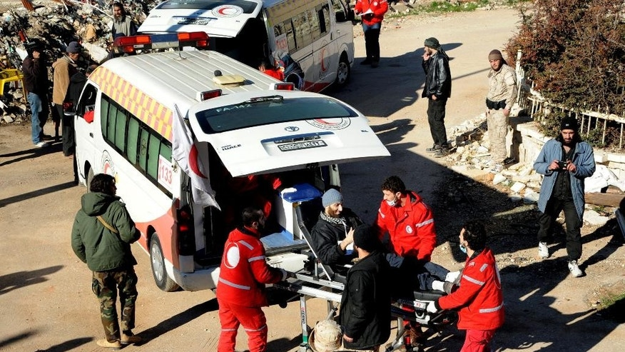 FILE - In this file photo released on December 28, 2015, by the Syrian official news agency SANA, Syrian Red Crescent workers carry a wounded Syrian opposition fighter, during an evacuation from the town of Zabadani, in Syria.  A young man has died of malnutrition and a surgeon killed by a sniper in two besieged towns in western Syria this past month in a stark reminder that sieges continue to kill Syrians despite international efforts to defuse them in halting negotiations in Europe. (SANA via AP, File)