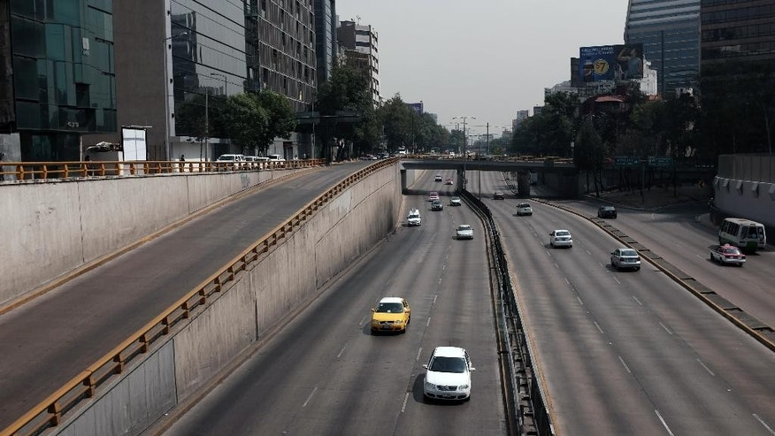Cars drive along what would usually be a very busy thoroughfare in Mexico City, Wednesday, April 6, 2016. City authorities have barred millions of vehicles from the streets due to a pollution alert. (AP Photo/Dario Lopez-Mills)