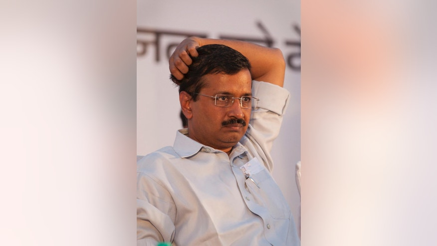 FILE- In this May 25, 2015 file photo, Delhi state Chief Minister Arvind Kejriwal and leader of Aam Aadmi Party, or Common Man's Party attends a public meeting to mark the party's 100 days government in the capital, in New Delhi, India. On Saturday, April 9, 2016, a disgruntled former party worker flung a shoe at Kejriwal at a press conference in New Delhi The shoe missed the target and the chief minister was unhurt.  (AP Photo/Tsering Topgyal, file)