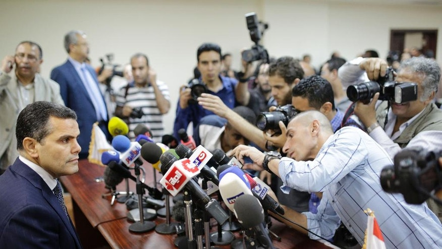 Journalists surround Egypt's Deputy Public Prosecutor Mustafa Suleiman, who headed an Egyptian delegation that was in Rome last week, as he prepares to speak during a press conference on slain Italian graduate student Giulio Regeni, at the prosecutor general's office,  in Cairo, Egypt, Saturday, April 9, 2016. (AP Photo/Amr Nabil)