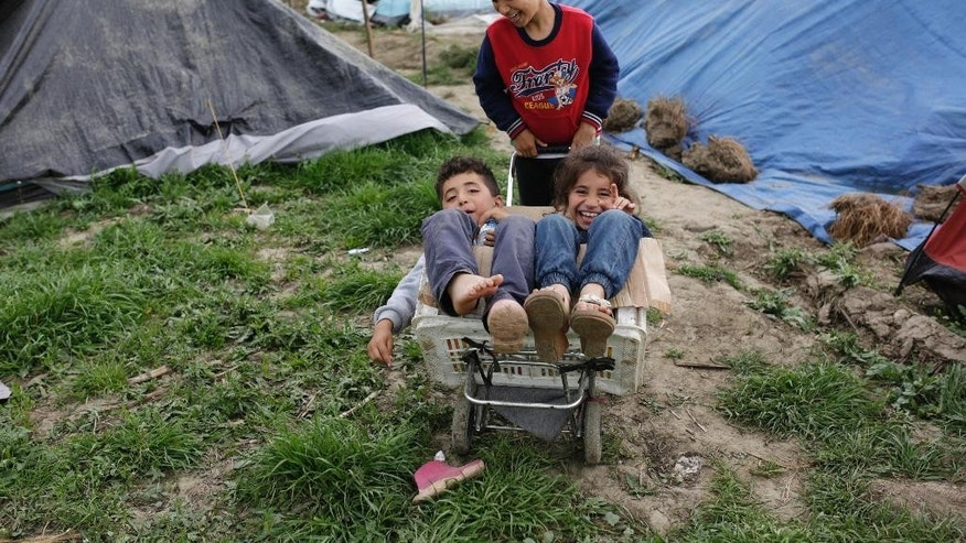 Migrant children play at the northern Greek border point of Idomeni, Greece, Saturday, April 9, 2016. More than 11,000 people have been stranded in Idomeni, an impromptu camp that has burgeoned right on the border with Macedonia, for weeks after Europe closed its land borders to migrants and refugees last month. (AP Photo/Amel Emric)