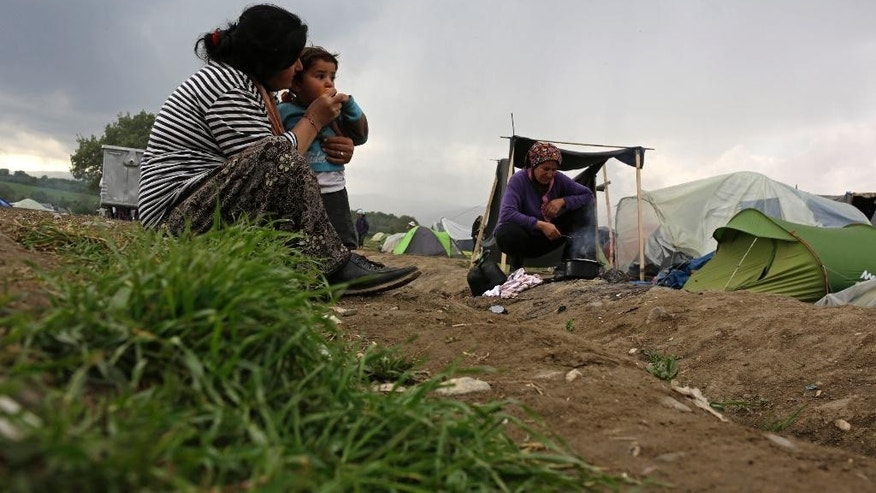 Migrant women with children sit on the ground near tents at the northern Greek border point of Idomeni, Greece, Saturday, April 9, 2016. More than 11,000 people have been stranded in Idomeni, an impromptu camp that has burgeoned right on the border with Macedonia, for weeks after Europe closed its land borders to migrants and refugees last month. (AP Photo/Amel Emric)