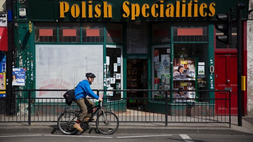 "A man cycles past a Polish Specialities shop in London, Tuesday, April 5, 2016. Britain's dynamic economy has attracted more people from Poland than any other single EU country, and they worry that they could be among the big losers if British voters opt for ""Brexit"" in the June 23 referendum. (AP Photo/Matt Dunham)"
