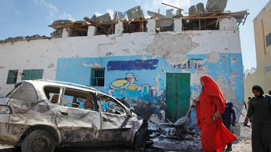 A female police officer inspects the scene of a car bomb attack outside a restaurant in the capital Mogadishu, Somalia Saturday, April 9, 2016. A Somali police official says two people have been killed in a car bombing at a restaurant where dozens of people were dining, in the capital Saturday.  (AP Photo/Farah Abdi Warsameh)