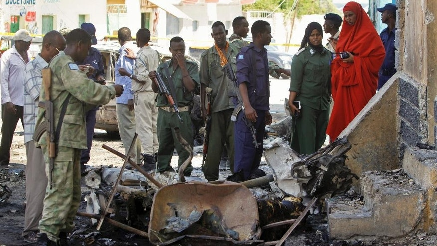 Security forces inspect the scene of a car bomb attack outside a restaurant in the capital Mogadishu, Somalia Saturday, April 9, 2016. A Somali police official says two people have been killed in a car bombing at a restaurant where dozens of people were dining, in the capital Saturday. (AP Photo/Farah Abdi Warsameh)