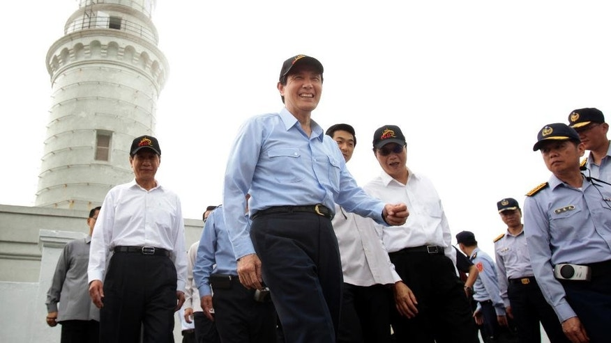 Taiwan's President Ma Ying-jeou, center, smiles as he leaves a lighthouse, background, during his visit to Pengjia Islet in the East China Sea, north of Taiwan, Saturday, April 9, 2016. Ma visited the small island to reassert Taiwan's sovereignty and its role in the contested region, one of the key issues of his administration that ends next month. Ma's visit to Pengjia, roughly 35 miles (56 kilometers) north of Taiwan proper, was his administration's second propaganda trip to an island in three weeks. It came four years after Ma last visited Pengjia to propose a plan to address territorial disputes between China, Taiwan and Japan over the nearby chain known as Senkaku in Japanese and Diaoyutai in Chinese. (AP Photo/Chiang Ying-ying)