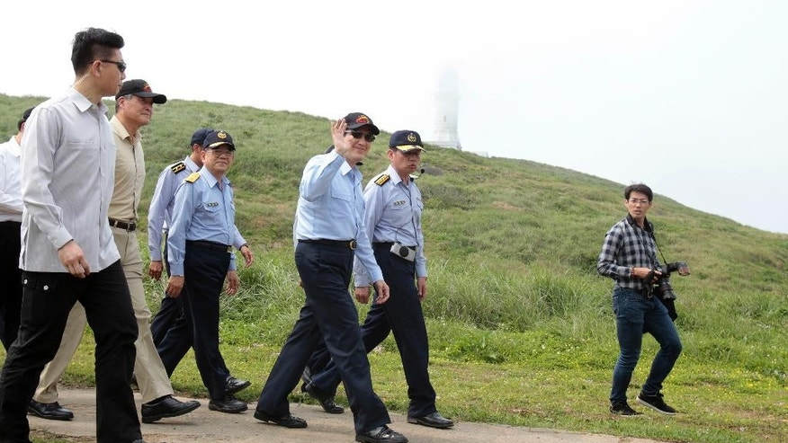 Taiwan's President Ma Ying-jeou, third from right, waves upon arrival at Pengjia Islet in the East China Sea, north of Taiwan, Saturday, April 9, 2016. Ma visited the small island to reassert Taiwan's sovereignty and its role in the contested region, one of the key issues of his administration that ends next month. Ma's visit to Pengjia, roughly 35 miles (56 kilometers) north of Taiwan proper, was his administration's second propaganda trip to an island in three weeks. It came four years after Ma last visited Pengjia to propose a plan to address territorial disputes between China, Taiwan and Japan over the nearby chain known as Senkaku in Japanese and Diaoyutai in Chinese. (AP Photo/Chiang Ying-ying)