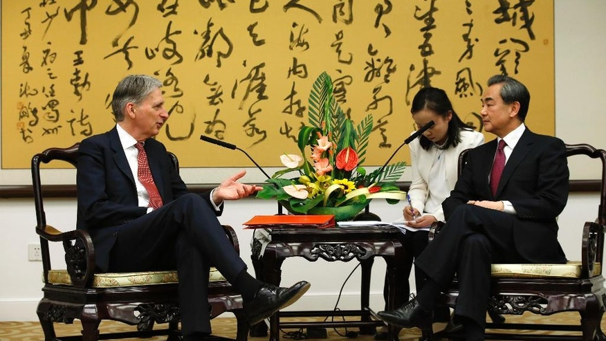British Foreign Secretary Philip Hammond, left, talks with Chinese Foreign Minister Wang Yi, right, during a meeting in Beijing Saturday, April 9, 2016. (Kim Kyung-Hoon/Pool Photo via AP)