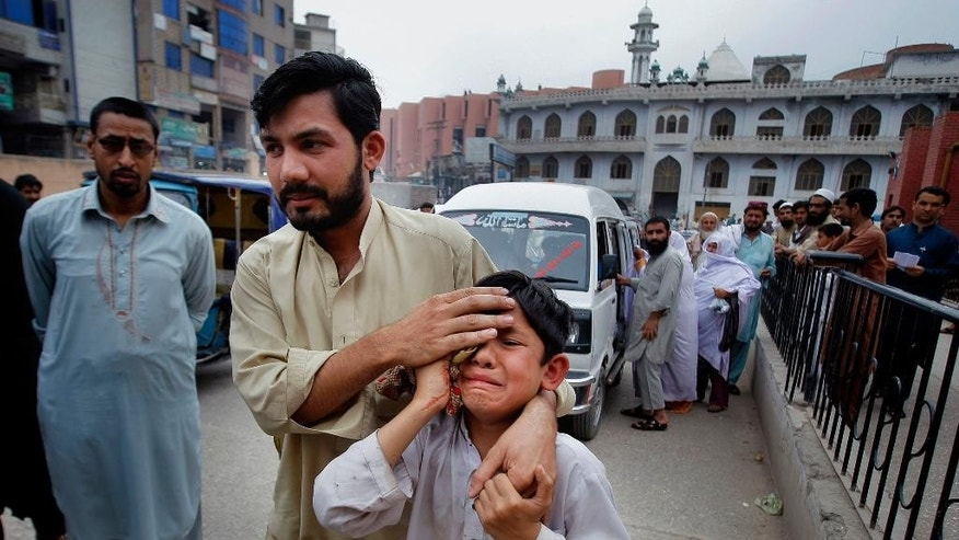 A man helps an injured boy to a hospital after an earthquake hit Peshawar, Pakistan, Sunday, April 10, 2016. A powerful earthquake rattled Pakistan's capital and other cities across the country on Sunday, causing panic among people but with no immediate reports of casualties or major damages. Pakistani official Arif Ullah told The Associated Press that the magnitude-7.1 quake was centered near Afghanistan's border with Tajikistan. (AP Photo/Mohammad Sajjad)