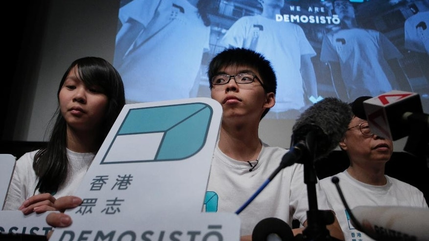 Hong Kong teen activist Joshua Wong, center, and members of their new political party Demosisto listen to reporter's questions as they officially unveiled during a press conference in Hong Kong, Sunday, April 10, 2016. Wong's new political party plans to field candidates in an upcoming election, marking the next step in the pro-democracy movement's evolution in the southern Chinese city. Wong and several other young activists who led pro-democracy protests that gripped Hong Kong for 79 days in late 2014. (AP Photo/Vincent Yu)
